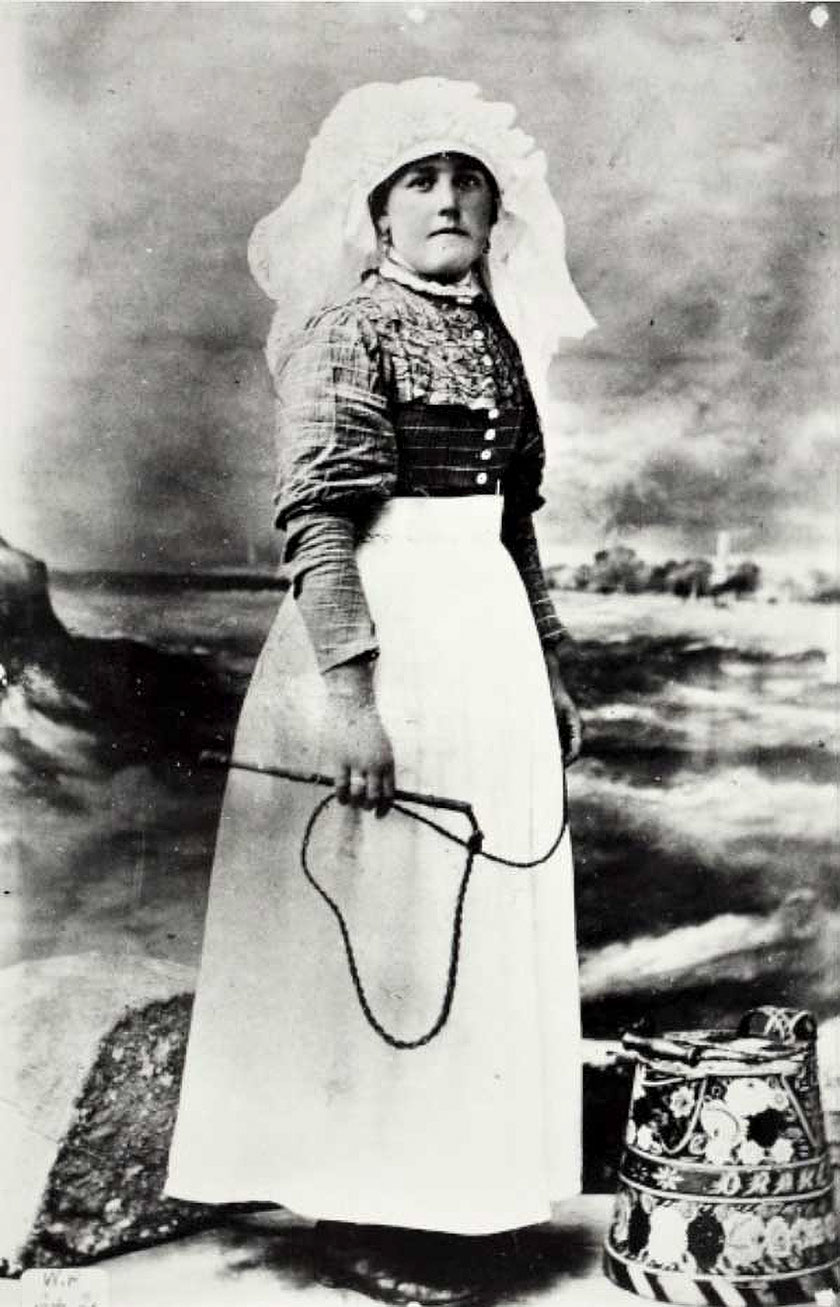 Boatwoman is holding a thrum, or cracking whip, used for signalling to other boats